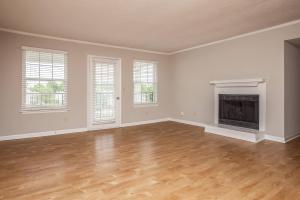 a living room with hard wood floors and a large window