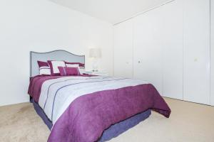 a bedroom with a purple blanket on a bed