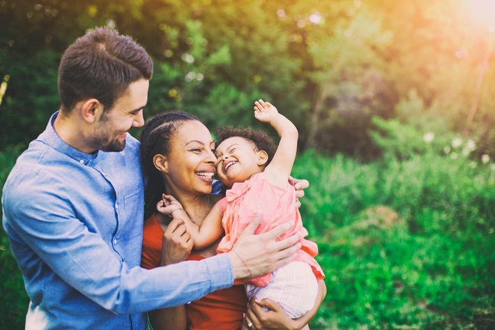 interracial-mixed-family-mom-dad-daughter-smiling-843909910.jpg