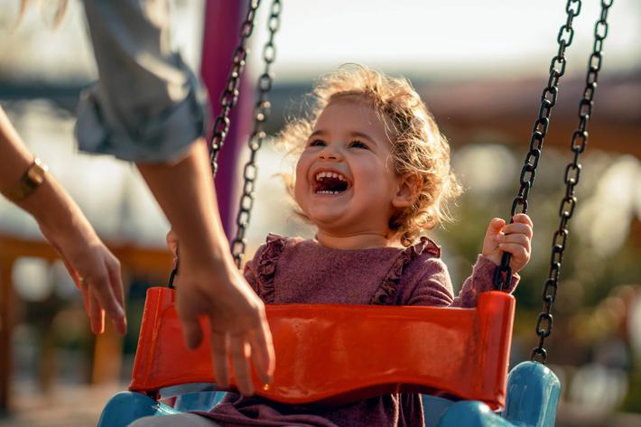toddler-girl-swing-laughing-smiling-1072630032.jpg
