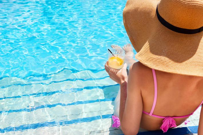 woman in hat pool side - iStock-639233998.jpg