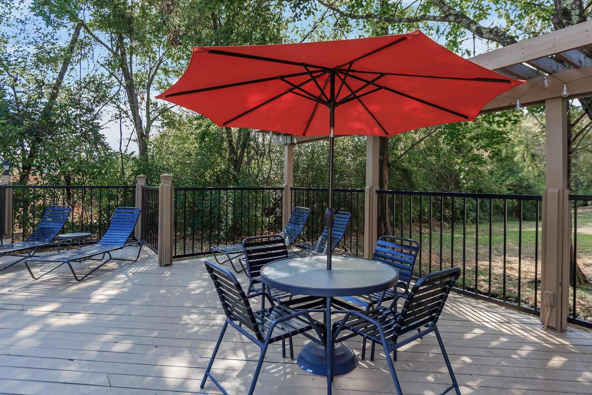 Patio table with umbrella and chaise lounges at Laurel Ridge Apartments in Chattanooga, TN