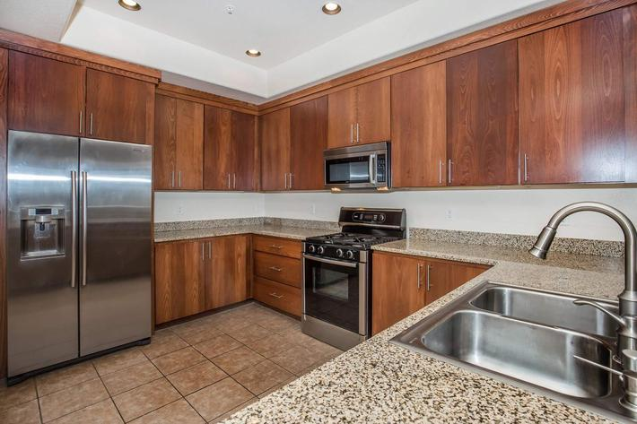 KITCHENS WITH STAINLESS STEEL APPLIANCES AND GRANITE COUNTERTOPS AT ECHELON AT CENTENNIAL HILLS IN LAS VEGAS