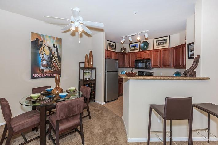 Ceiling Fan, Breakfast Bar, and Carpeted Floors in Homes at The Preserve Apartments in North Las Vegas, Nevada