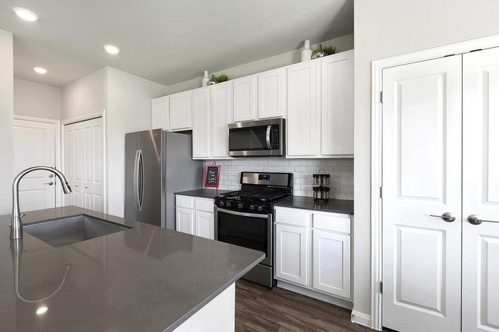 Georgetown, TX Apartments - Rivers Edge Kitchen with Stainless Steel Appliances, Large Island, and Double Door Pantry