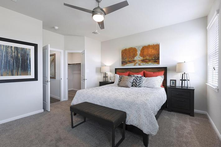 Three Bedroom Apartments in Georgetown, TX - Rivers Edge Bedroom with Walk-in Closet, Ceiling Fans, and Lush Carpet Floors