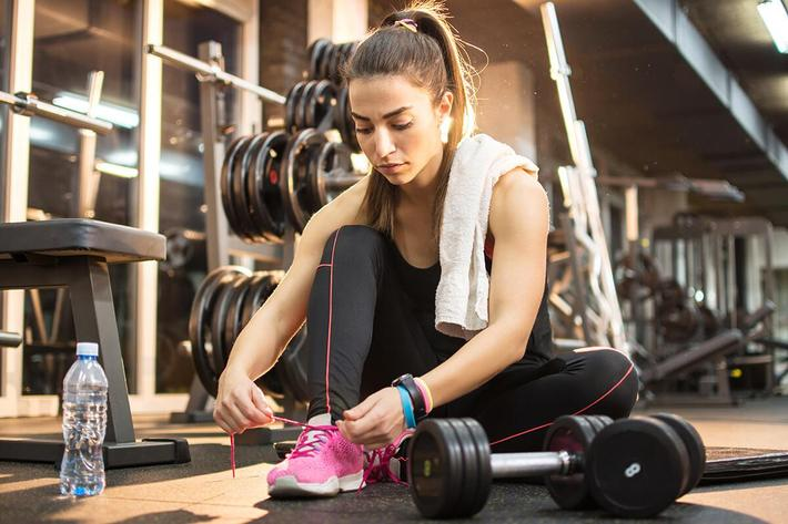 Young sporty woman tying shoes while sitting on floor in gym GettyImages-845914314.jpg