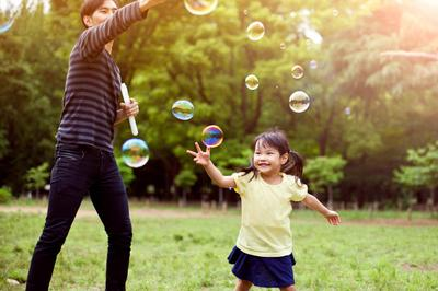 Father and daughter having fun in park with Soap Bubbles iStock-501485932.jpg