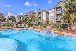 Grand swimming pool and lounging chairs in The Avenue apartments for rent in Nederland