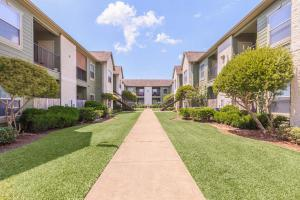 Central view of The Avenue apartment complex with spotless sidewalks and lush garden landscaping