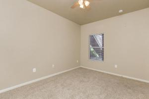 Bedroom with tan carpet, ceiling fan, and window with blinds