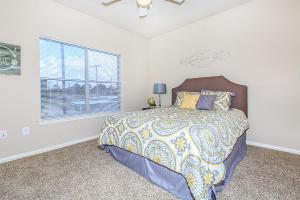 Furnished bedroom with double bed, ceiling fan, and large windows