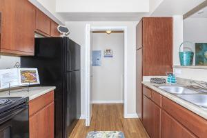 Galley-style kitchen with brown cabinetry, black appliances, and access to full-size washer/dryer