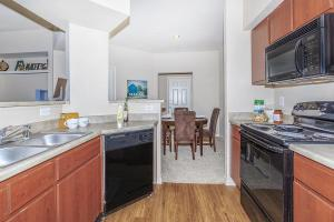 Kitchen with hardwood-style floors, black dishwasher and view of carpeted dining area