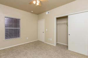 Bedroom with carpeted floors, walk-in closet, and ceiling fan
