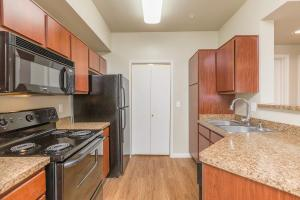 Galley-style kitchen with electric appliances and wood cabinets