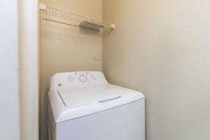 Laundry closet with full-size washer/dryer and shelf for extra storage