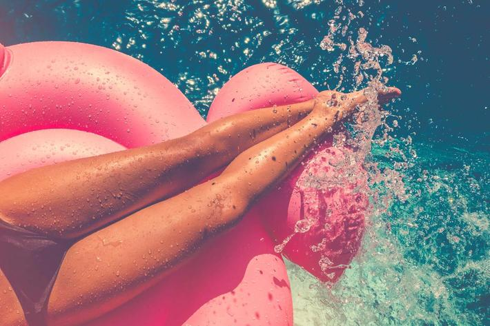 Woman floating on a pink inflatable in swimming pool. iStock-657181200.jpg