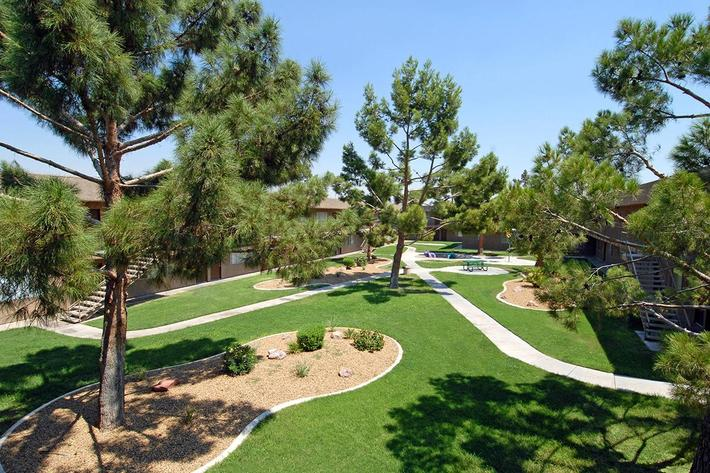 take in the breeze under the shade trees at Bella Estates Apartment Homes